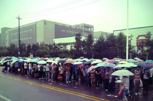 Arbeiders staan voor de Foxconn-fabriek in de rij.