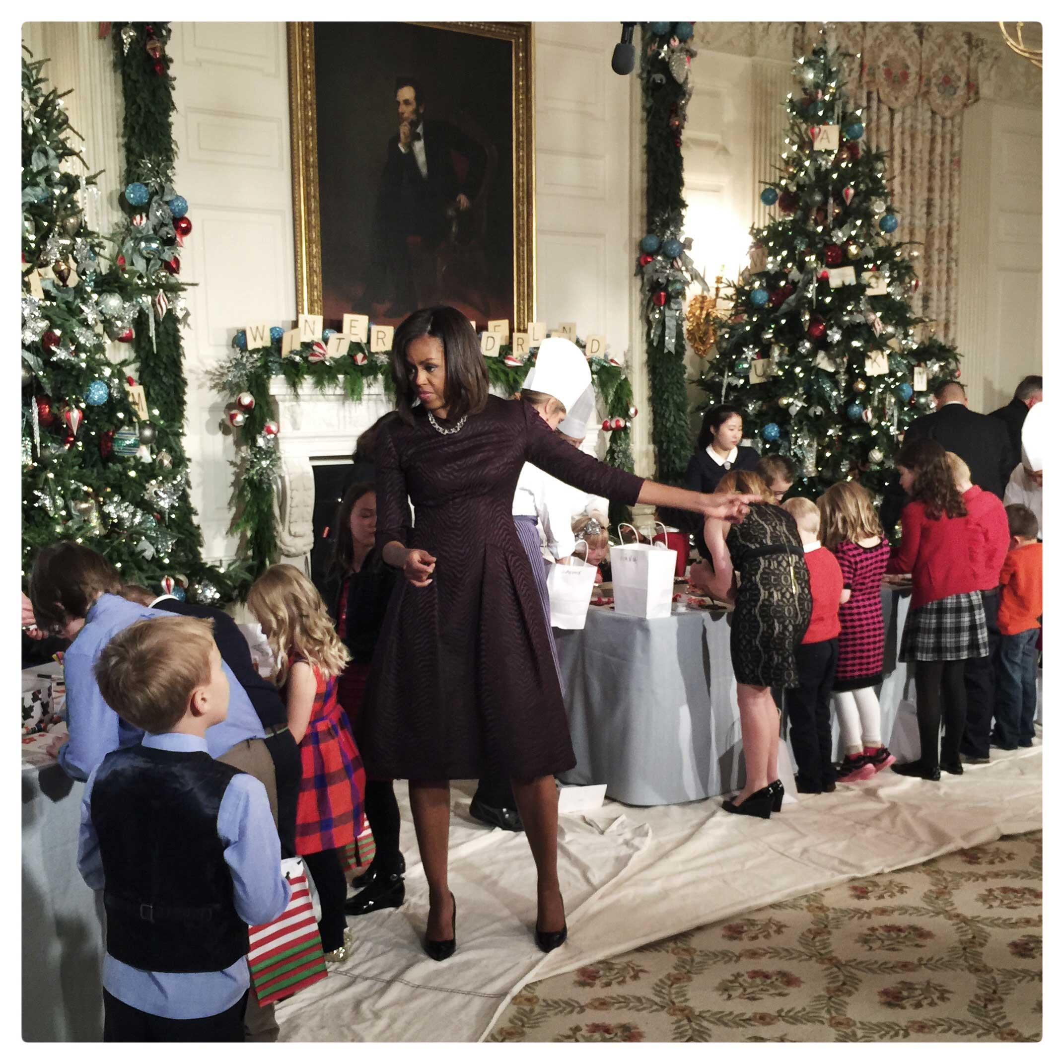 Michelle Obama pakt samen met kinderen de kerstcadeau's in.