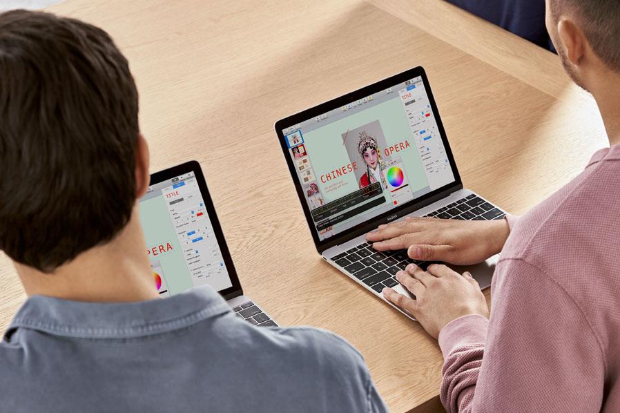 Foto: Twee mannen zitten naast elkaar aan een tafel. Ze werken allebei in Keynote, ieder op zijn eigen MacBook. De man aan de rechterkant gebruikt VoiceOver.